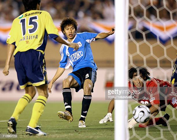 China's Dalian Shide FC midfielder Zhu Ting shoots the ball to score the team's second goal between Japanese club JEF United Chiba goalie Masahiro...
