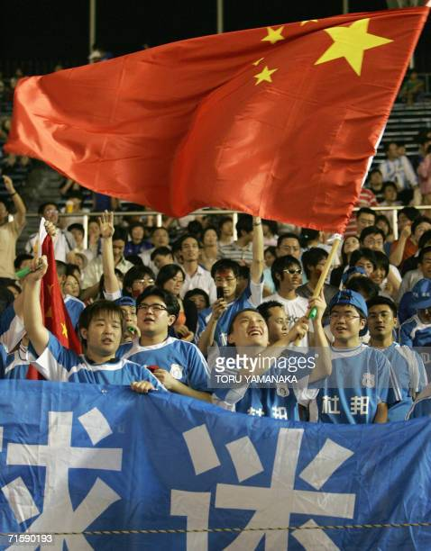 Chinese supporters cheer as they wave a national flag before the A3 Champions Cup 2006 match between China's Dalian Shide FC and Japan's JEF United...