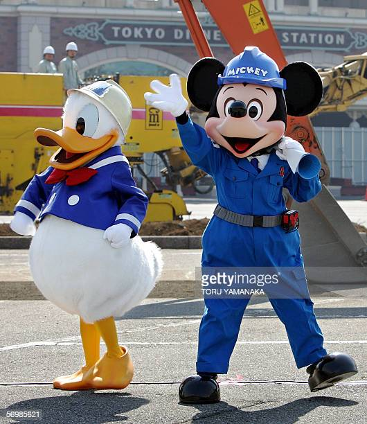 Disney characters Mickey Mouse and Donald Duck clad in hard hats at construction work take part in a ceremony marking construction of a new hotel at...