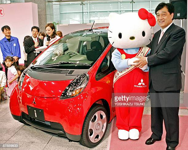 Japanese auto giant Mitsubishi Motors President Osamu Masuko shakes hands with famous cartoon character Hello Kitty next to the company's stylish...