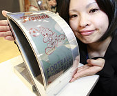 Japan's computer giant Fujitsu employee displays the prototype model of an electronic paper display that is flexible and does not blur even if it is...