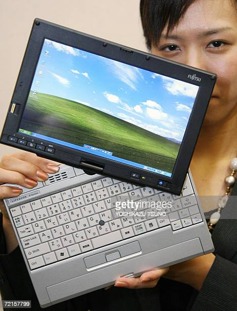 Japan's computer giant Fujitsu employee Miho Hirasawa displays the company's new tablet PC 'FMVLifebook FMVP8230' equipped with Intel's 12 GHz Core...