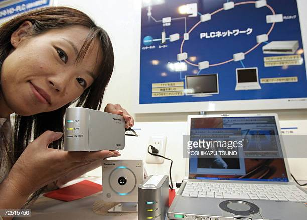 Japan's electronics giant Matsushita Electric Industrial employee Satoko Kubo displays the power line ethernet adaptor 'HDPLC' allowing to create...
