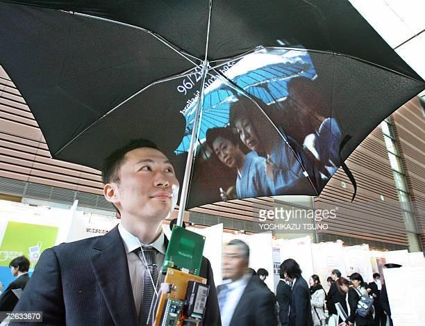 Japan's Keio University doctoral student Takashi Matsumoto displays the prototype model of the image or net browsing umbrella 'Pileus' to make rainy...