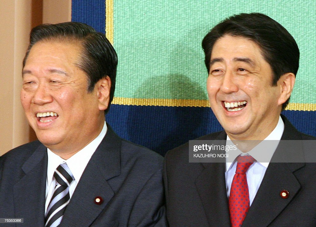 Japan's Prime Minister and ruling Liberal Democratic Party President Shinzo Abe (R) and main opposition Democratic Party of Japan President Ichiro Ozawa (L) smile after a debate for the upcoming Upper House poll at Japan National Press Club in Tokyo, 11 July 2007. Embattled Prime Minister Shinzo Abe was to hold debate with leaders of other parties ahead of July 29 elections which will be a key test for the government..