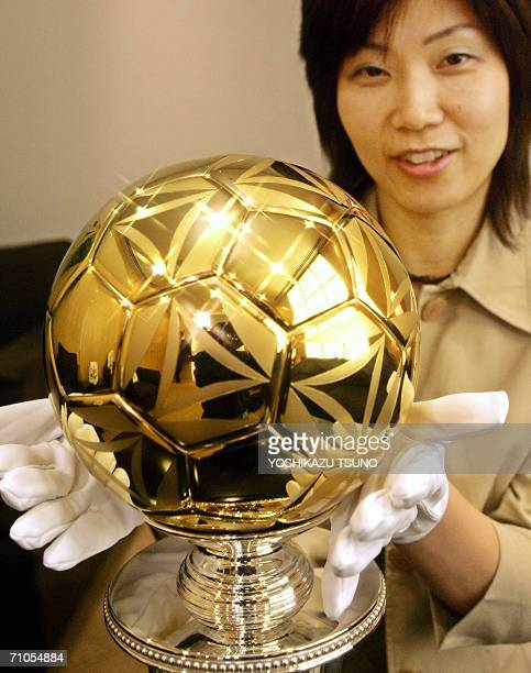 Japan's Takashimaya department store employee Yasuyo Takigawa displays the 2006 million yen pure gold soccer ball which is the same size as an...