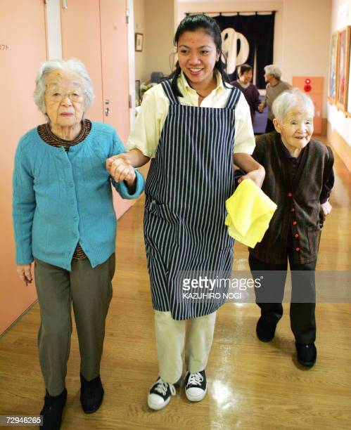 Maria Falqueza from the Philippine capital of Manilla walks with elderly Japanese women to support their walking priro to an yearend party in a care...