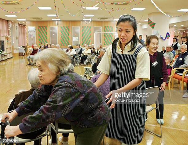 Maria Falqueza from the Philippines capital of Manilla supports a Japanese elderly woman prior to a yearend party in a care support facility in...
