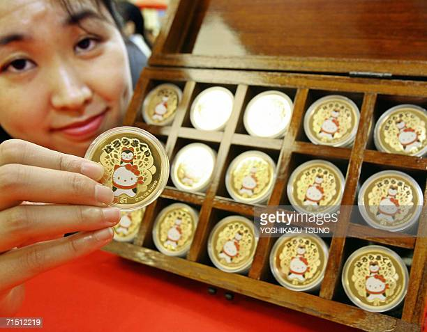 Mitsukoshi department store employee displays a box of Hello Kitty designed Tsubaruan oneounce silver coins coated with gold minted by Australia's...