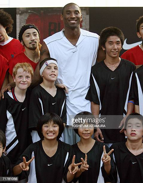 NBA's Los Angeles Lakers' star shooting guard Kobe Bryant poses with junior basketball players during his basketball clinic 'Kobe81 Asia Tour Summer...