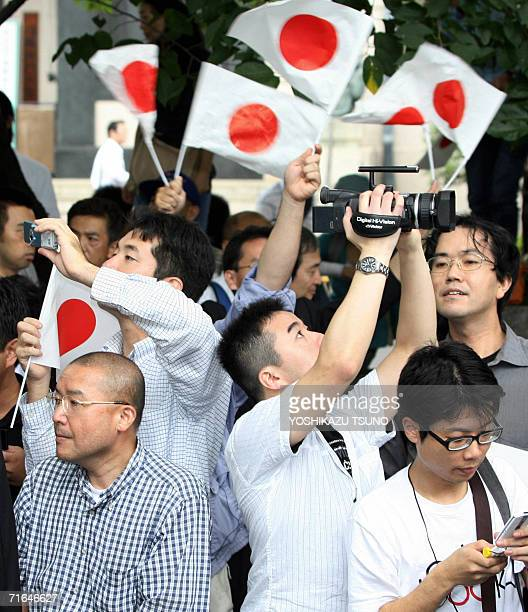 People wave Japanese national flags as Prime Minister Junichiro Koizumi visits the Yasukuni war shrine in Tokyo 15 August 2006 on the anniversary of...
