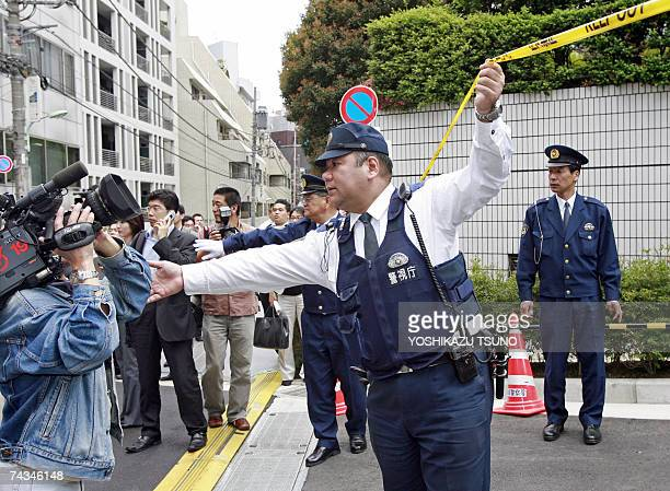 Police officers cordon off the area from the press in front of the dormitory for Diet members where Japanese Agriculture Forestry and Fisheries...