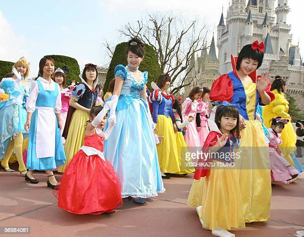 Some 300 girls and women in clad of Disney characters' princesses such as Cinderella Snow White parade before a castle for the celebration of Girls'...