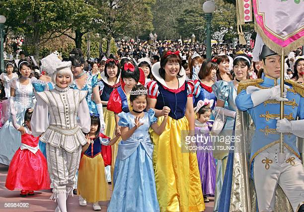 Some 300 girls and women in clad of Disney characters' princesses such as Cinderella Snow White parades before a castle for the celebration of Girls'...