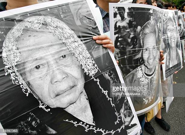 Supporters hold portraits of Chinese Philippine South Korean and Taiwanese former 'comfort women' who were sex slaves for Japanese soldiers during...