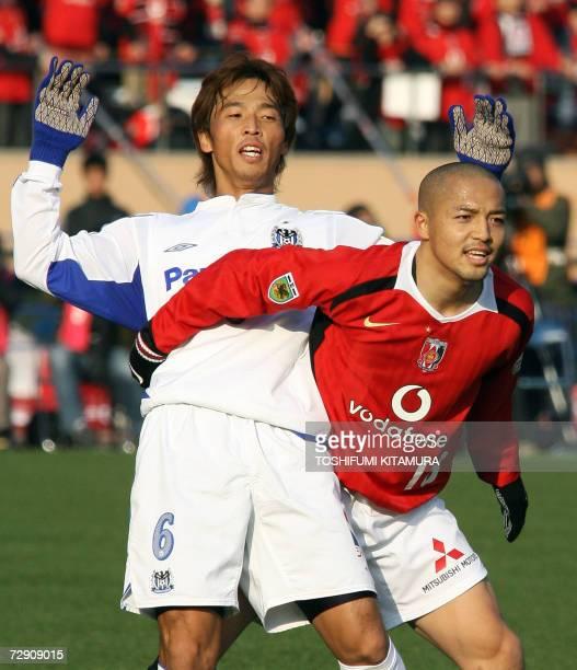 Urawa Reds midfielder Shinji Ono holds Gamba Osaka captain and defender Satoshki Yamaguchi during the 86th Emperor's Cup final match in Tokyo 01...