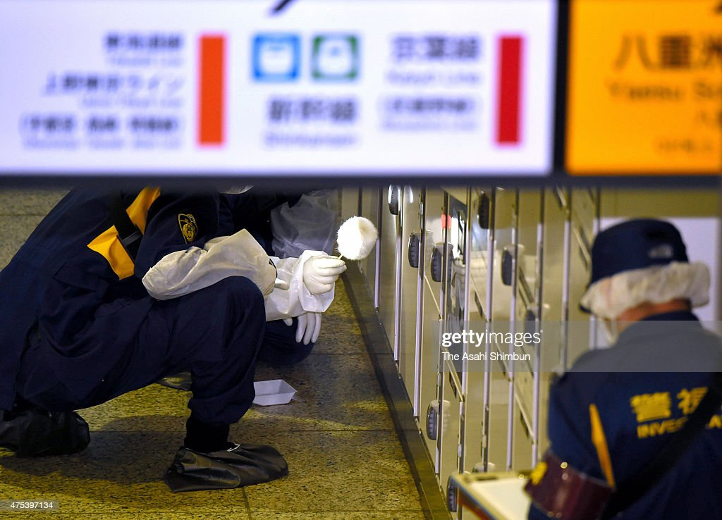 Tokyo Metropoliltan Police forensic team members investigate the locker where the suitcase contains a female body was found at Tokyo Station on May...