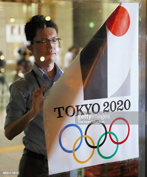 A Tokyo Metropolitan government staff removes a poster of the 2020 Tokyo Olympics emblem at the headquarters after the Organising Committee...