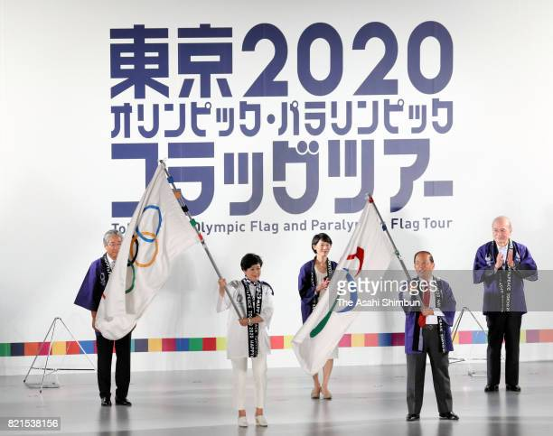 Tokyo Metropolitan Governor Yuriko Koike and Tokyo 2020 Organising Committee Director General Toshiro Muto wave the Olympic and Paralympic flags...