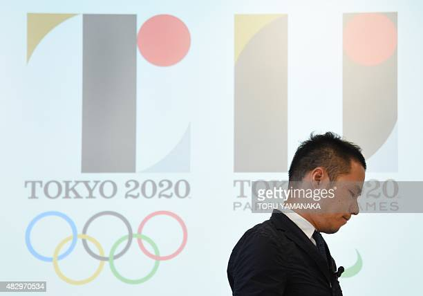 Tokyo Olympic logo designer Kenjiro Sano stands in front of the logo as he leaves a press conference at the headquarters of Tokyo 2020 in Tokyo on...