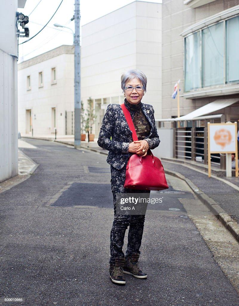 Street portrait of a stylish elderly Japanese woman in Tokyo, Japan.