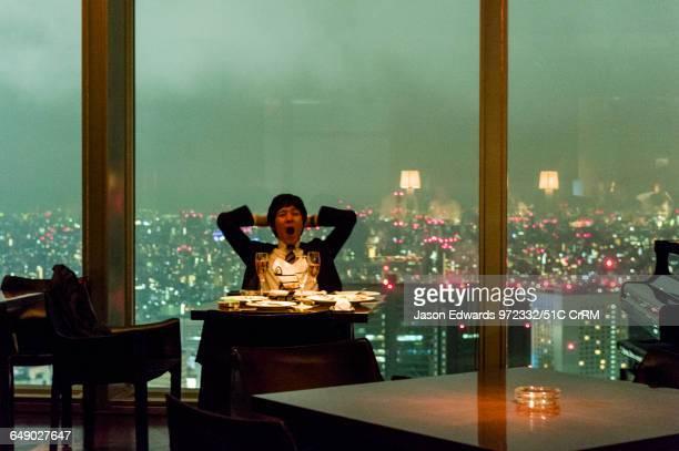 Tokyo salaryman yawning in a late night bar overlooking the city skyline