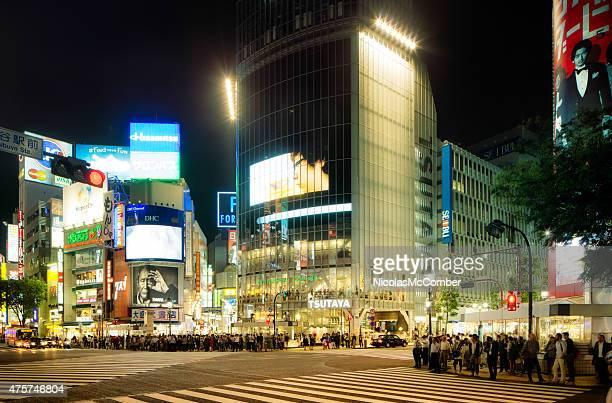 東京の渋谷交差点にて夜の群集をクロス