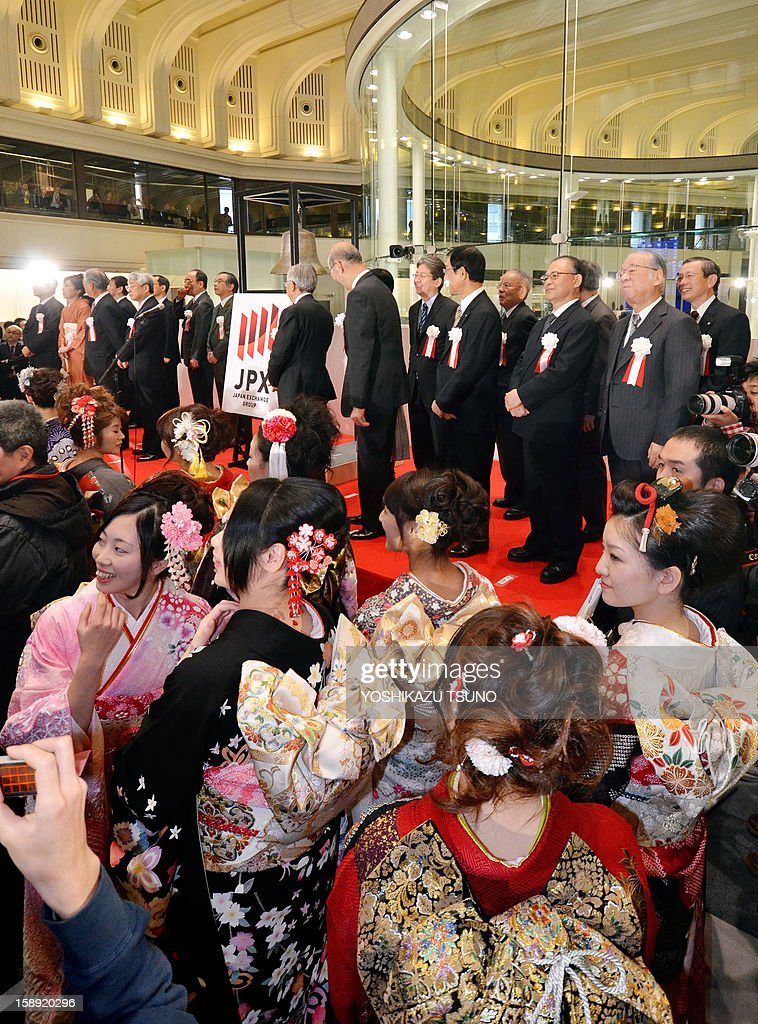 Tokyo Stock Exchange executives and kimono clad employees react as the share prices of the Tokyo Stock Exchange opens higher at the opening ceremony of the first trading day of the year at the Tokyo Stock Exchange on January 4, 2013 after the New Year's holidays. Japanese share prices rose 270.92 points to close at 10,666.10 points at the morning session of the Tokyo Stock Exchange, as the yen tumbled on relief over a US deal to avert the 'fiscal cliff' of tax hikes and huge spending cuts. AFP PHOTO / Yoshikazu TSUNO