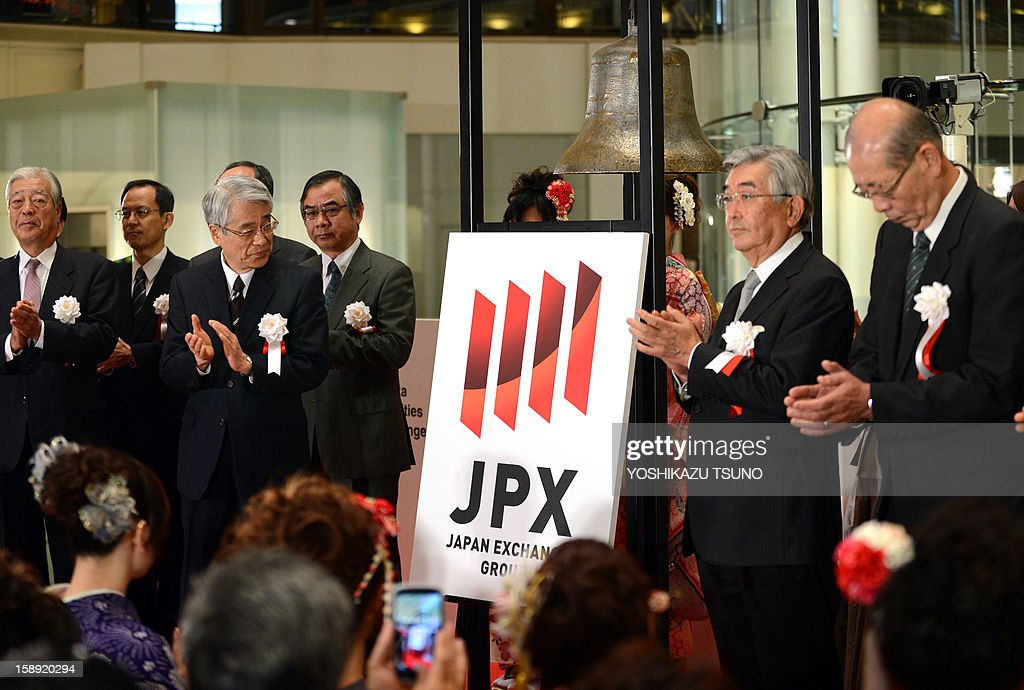 Tokyo Stock Exchange executives applaud as the new logo mark of the Japan Exchange Group, Tokyo Stock Exchange and Osaka Stock Exchange which were merged on January 1, is displayed at the opening ceremony of the first trading day of the year at the Tokyo Stock Exchange on January 4, 2013 after the New Year's holidays. Japanese share prices rose 270.92 points to close at 10,666.10 points at the morning session of the Tokyo Stock Exchange, as the yen tumbled on relief over a US deal to avert the 'fiscal cliff' of tax hikes and huge spending cuts. AFP PHOTO / Yoshikazu TSUNO