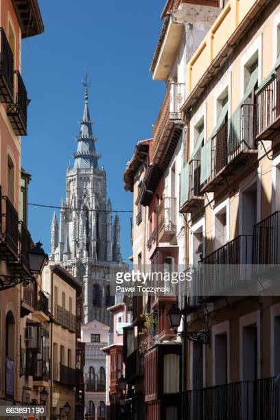 Toledo Cathedral seen from a narrow street filled with traditional medieval houses, Toledo, Spain