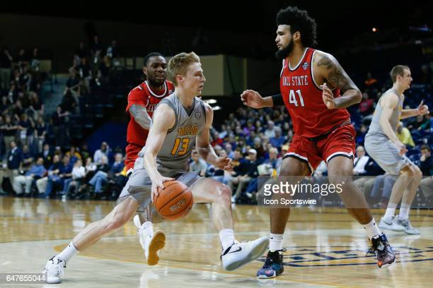 Toledo Rockets guard Jaelan Sanford drives the baseline against Ball State Cardinals center Trey Moses during a regular season basketball game...