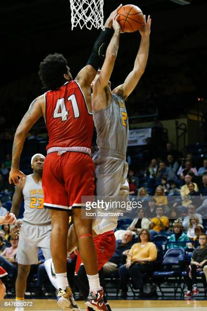 Toledo Rockets guard Jordan Lauf shoots over Ball State Cardinals center Trey Moses during a regular season basketball game between the Ball State...