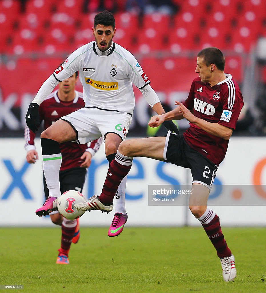 Tolga Cigerci (L) of Moenchengladbach is challenged by Timmy Simons of Nuernberg during the Bundesliga match between 1. FC Nuernberg and VfL Borussia Moenchengladbach at Easy Credit Stadium on February 3, 2013 in Nuremberg, Germany.