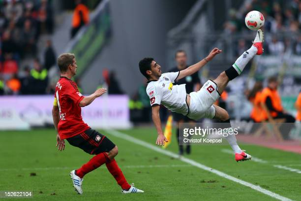 Tolga Cigerci of Moenchengladbach plays an overhead kick and Lars Bender of Leverkusen watches him during the Bundesliga match between Bayer 04...