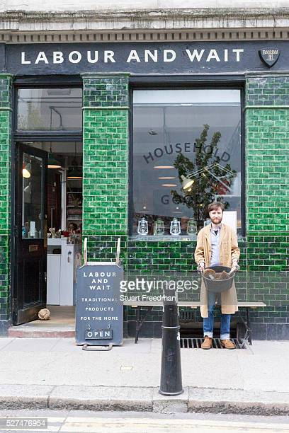 Tom a shop assistant outside the fashionable hardware shop Labour and Wait London UK Labour and Wait sell new and vintage industrial and utility...