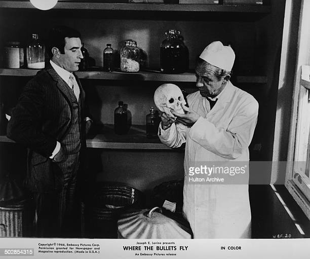 Tom Adams listens to Sidney James in a scene from the movie 'Where the Bullets Fly' circa 1966