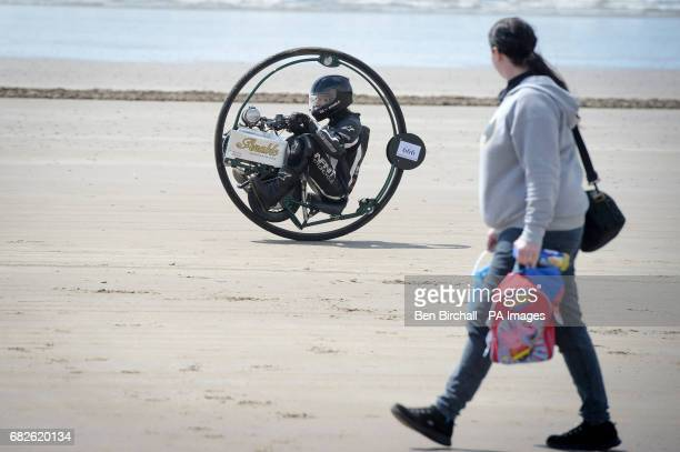 Tom Anable from Lincolnshire warmsup his monowheel bike before the Straightliners 'Top Speed' event at Pendine Sands Wales where riders and drivers...