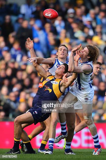 Tom Barrass of the Eagles contests a mark against Drew Petrie and Ben Brown of the Kangaroos during the round 16 AFL match between the West Coast...