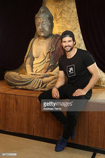 Tom Beck sits next to a a giant Buddha sculpture at John Reed Fitness on July 14 2016 in Bonn Germany John Reed Fitness launches today their first...