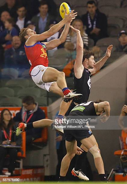 Tom Bell of the Lions attempts a spectacular mark over Lachie Plowman and Sam Rowe of the Blues during the 2016 AFL Round 11 match between the...