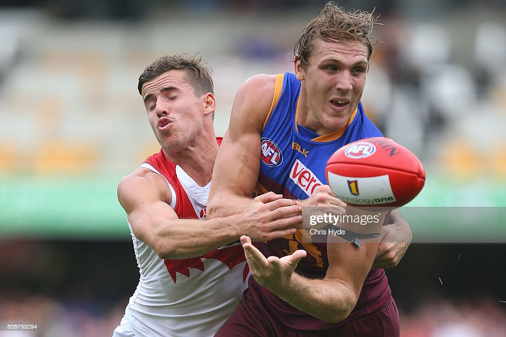 Tom Bell of the Lions handballs during the round six AFL match between the Brisbane Lions and the Sydney Swans at The Gabba on May 1, 2016 in Brisbane, Australia.