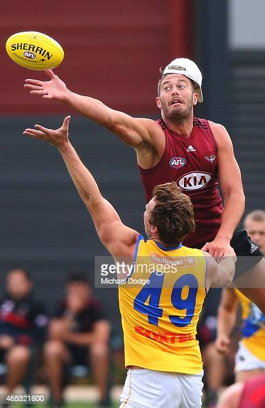 Tom Bellchambers of the Bombers taps the ball over Ayce Cordy of Williamstown during an Essendon Bombers match simulation training session against...