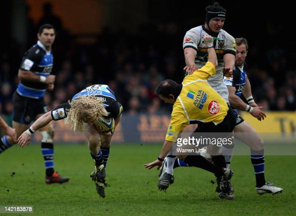 Tom Biggs of Bath makes a break as Referee Martin Fox is floored by Mark Sorenson of Northampton Saints during the Aviva Premiership match between...