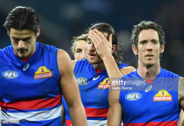 Tom Boyd Marcus Bontempelli and Robert Murphy of the Bulldogs look dejected after losing the round nine AFL match between the Geelong Cats and the...