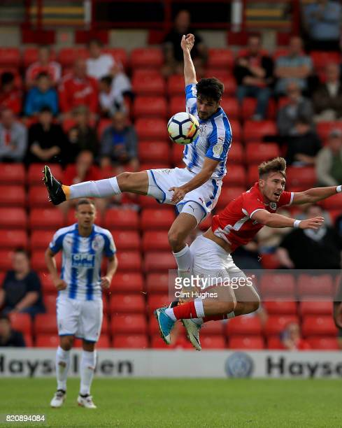 Tom Bradshaw of Barnsley and Christopher Schindler of Huddersfield Town contest a header during the pre season friendly at Oakwell Stadium on July 22...