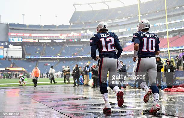 Tom Brady and Jimmy Garoppolo of the New England Patriots run onto the field before a game against the New York Jets at Gillette Stadium on December...