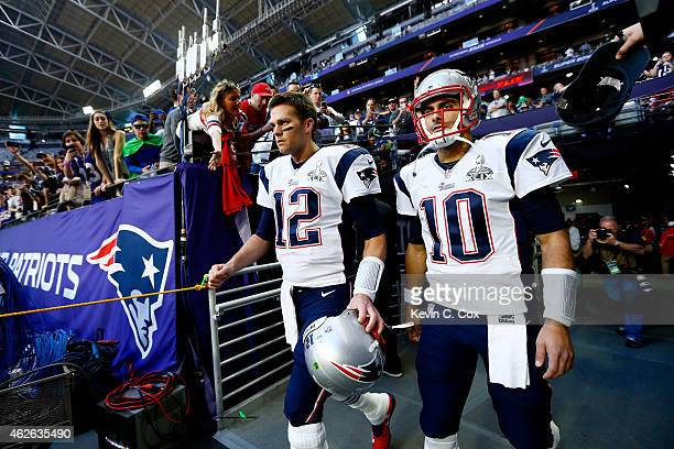 Tom Brady and Jimmy Garoppolo of the New England Patriots walk to the field before Super Bowl XLIX against the Seattle Seahawks at University of...