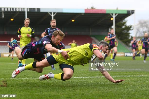 Tom Brady of Leicester Tigers dives past Matt Jess of Exeter Chiefs to score his team's first try during the AngloWelsh Cup Final between Exeter...
