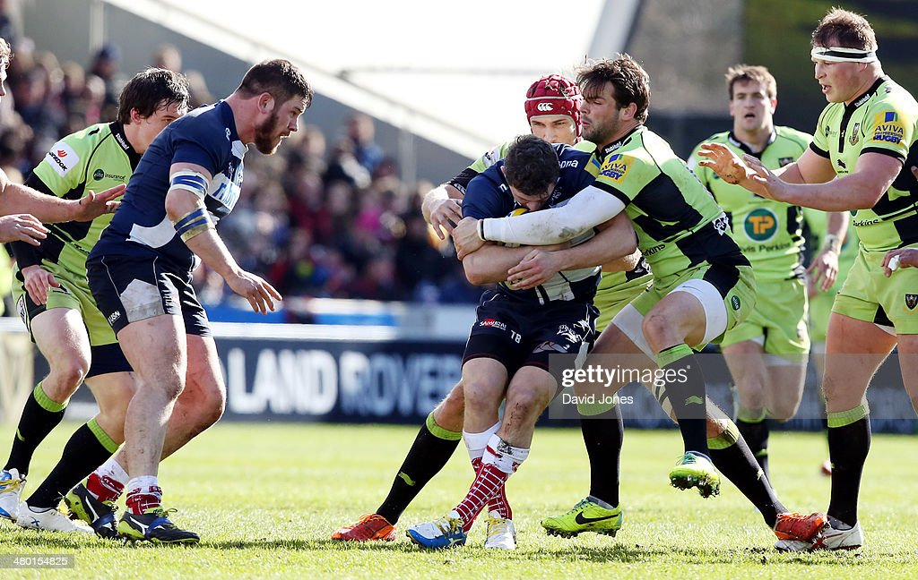 Tom Brady of Sale Sharks is hald by Ben Foden of Northampton Saints during the Aviva Premiership match between Sale Sharks and Northampton Saints at the A J Bell Stadium, on March 22, 2014 in Salford, England