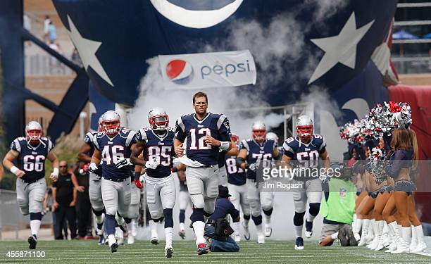 Tom Brady of the New England Patriots and teammates run onto the field before a game against the Oakland Raiders at Gillette Stadium on September 21...